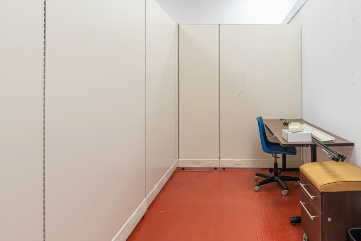 Picture of Shared Studio Space #1. Desk, Blue Chair on Wheels and a small cabinet on wheels in a room with high ceilings and office cubical walls